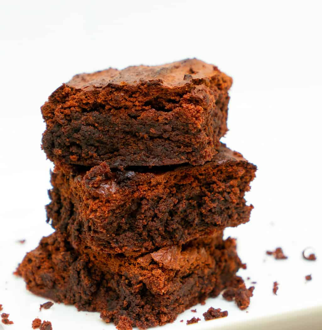keto coconut flour brownies stacked on a white plate