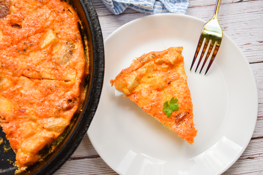 keto frittata in cast iron skillet with slice serve on white plate close up