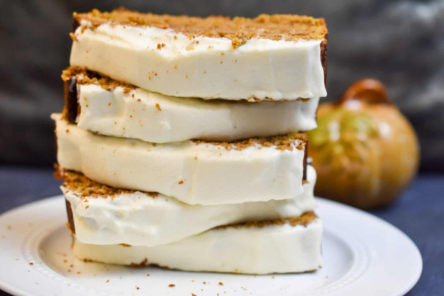 keto pumpkin bread with frosting stacked on a white pate