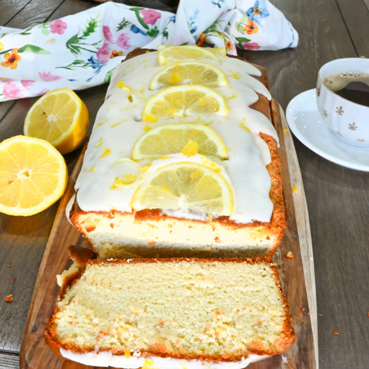 keto lemon pound cake loaf sliced on a wood board and ready to serve