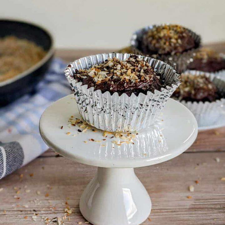 keto chocolate coconut cupcake on a small white pedestal plate