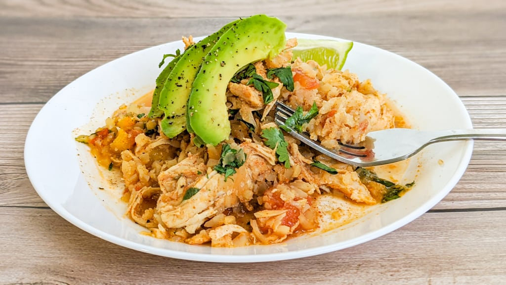Keto Mexican Cauliflower Rice and Chicken Topped with Avocado on white plate with fork fit to serve