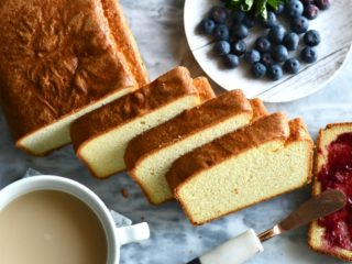 Keto coconut flour pound cake sliced on a marble slab with blueberries next to it