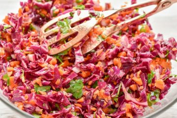 This Keto Red Cabbage And Carrot Slaw recipe is the perfect spring & summer side dish. It features a tangy apple cider vinaigrette that keeps this slaw light, crunchy, and slightly spicy.   It's a beautiful combination of colors, textures, and flavors.
