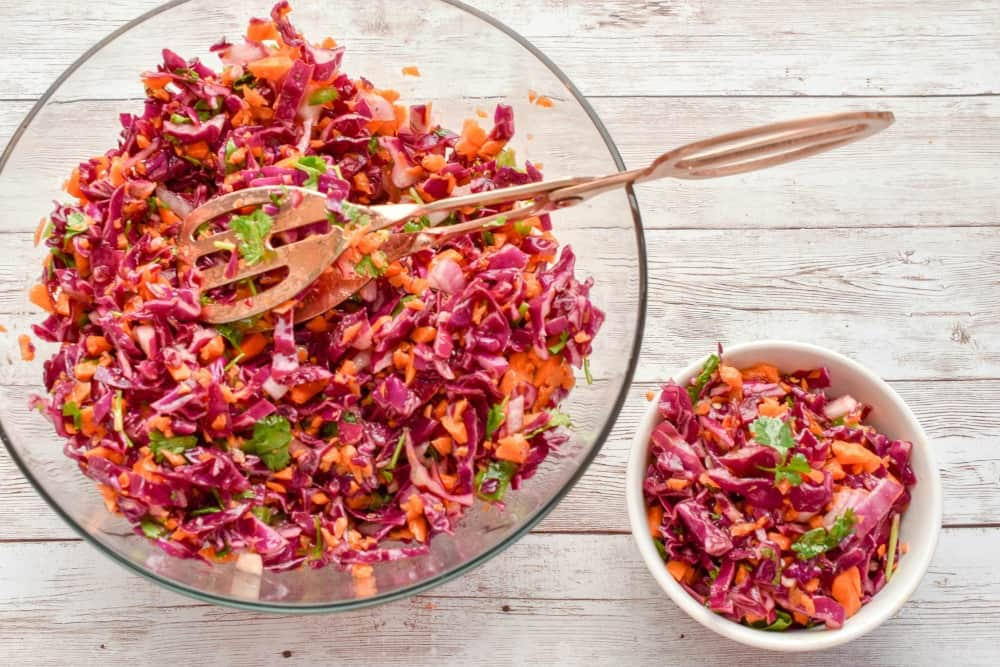 This Keto Red Cabbage And Carrot Slaw recipe is the perfect spring & summer side dish. It features a tangy apple cider vinaigrette that keeps this slaw light, crunchy, and slightly spicy.  It's a refreshing salad that packs a lot of nutrition.