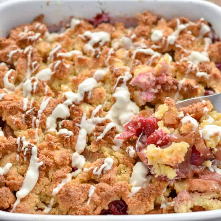 keto apple cranberry cobbler in a white baking dish being served