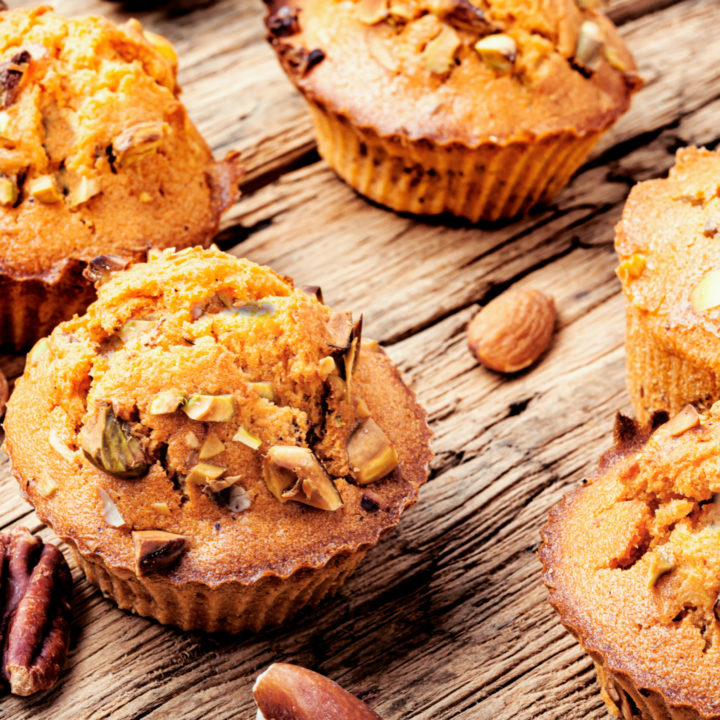 keto high fiber muffins on a wooden table with scattered nuts