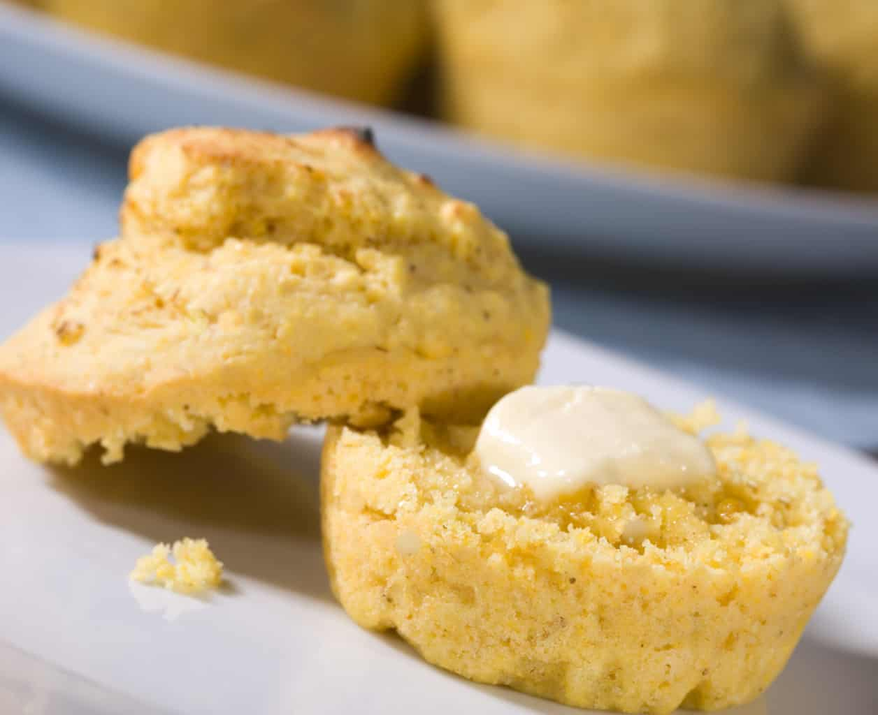 one almond flour cornbread muffin on a white plate split with butter on top