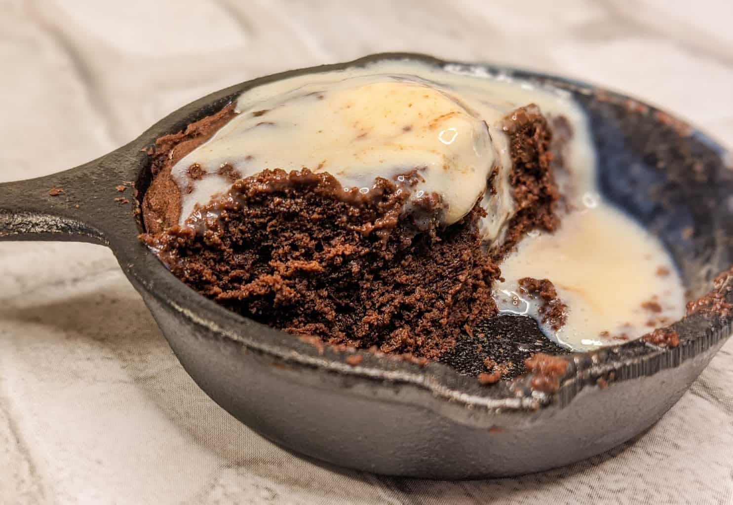 coconut flour keto brownie a la mode in a skillet mini with ice cream melted