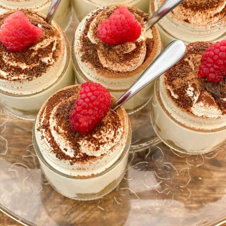 upclose individual keto tiramisu cheesecakes with spoons and raspberries on a wood board