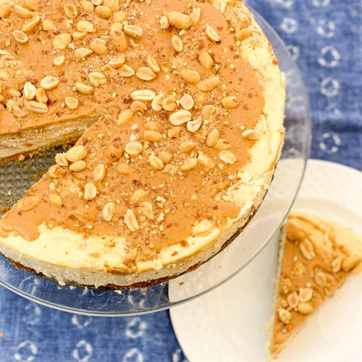 keto peanut butter swirl cheesecake featured image shows a cheesecake on a clear stand with a slice removed