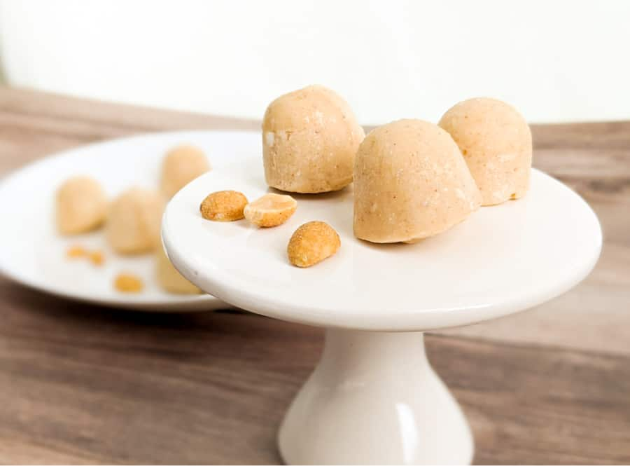 Cream Cheese Peanut Butter Fat Bombs on White Pedestal with Peanuts