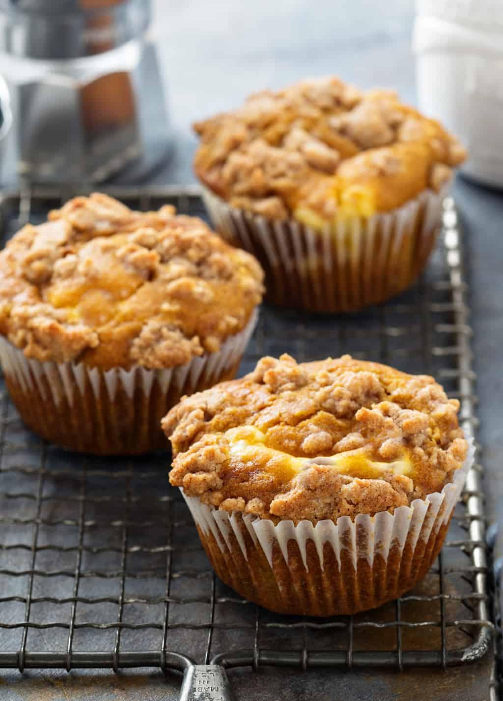 keto pumpkin cheesecake muffins on a baking rack cooling