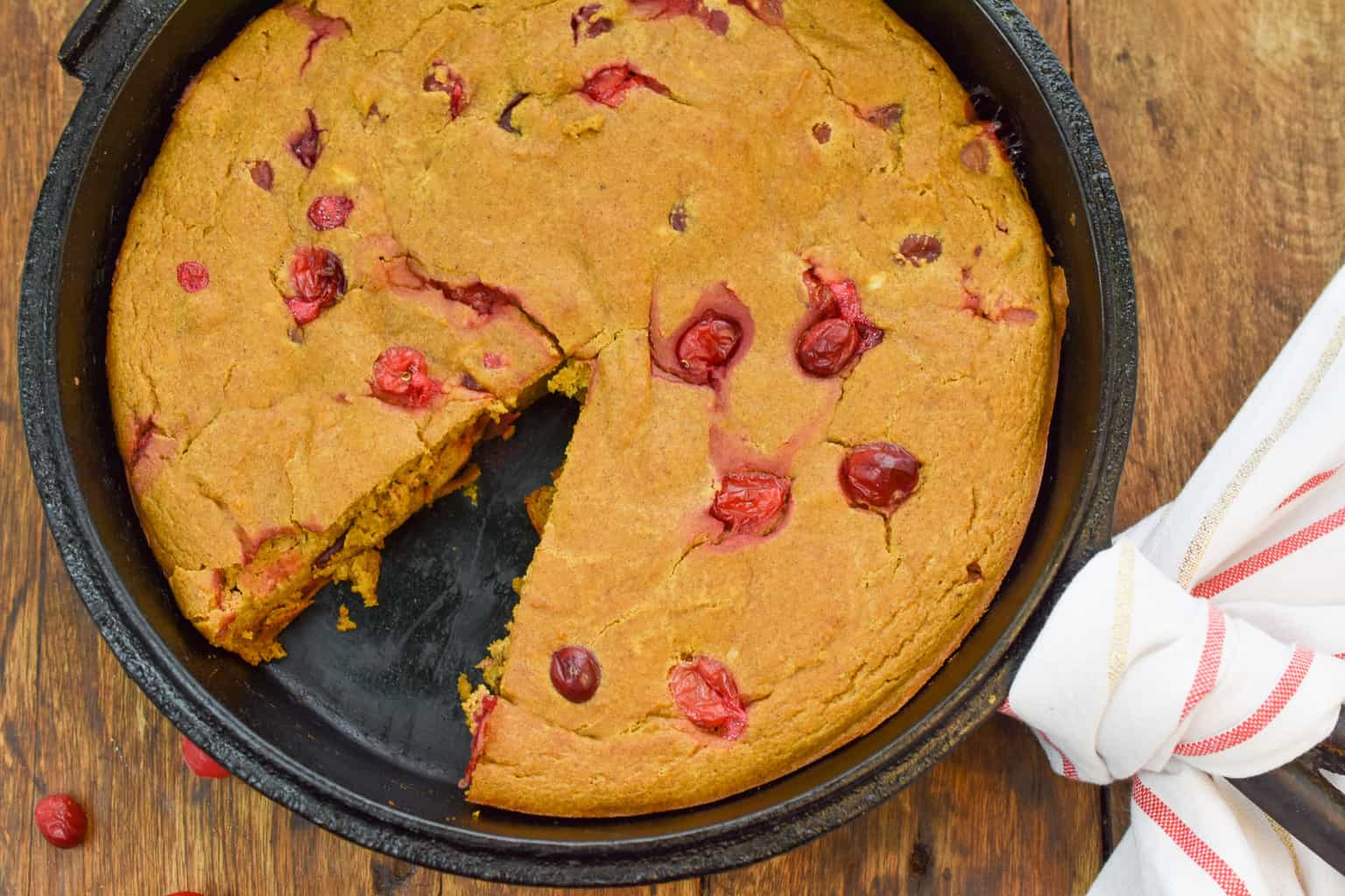 keto pumpkin cranberry cake on wood board with a slice missing
