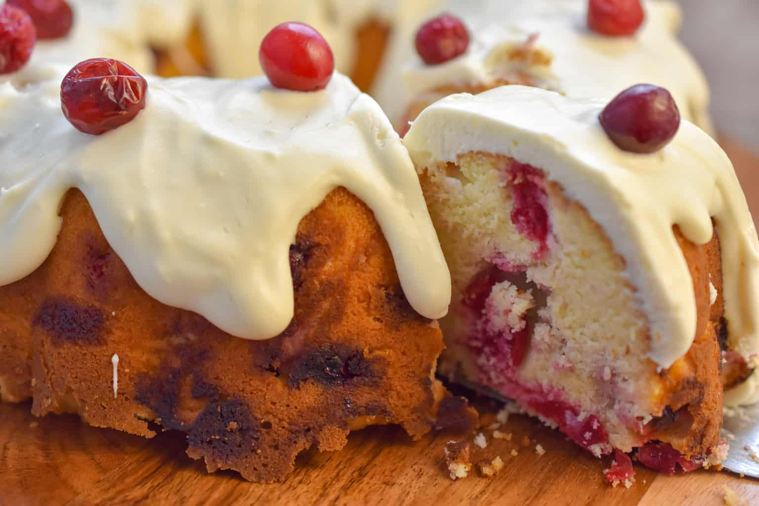 keto cranberry cake being sliced on wood cake stand