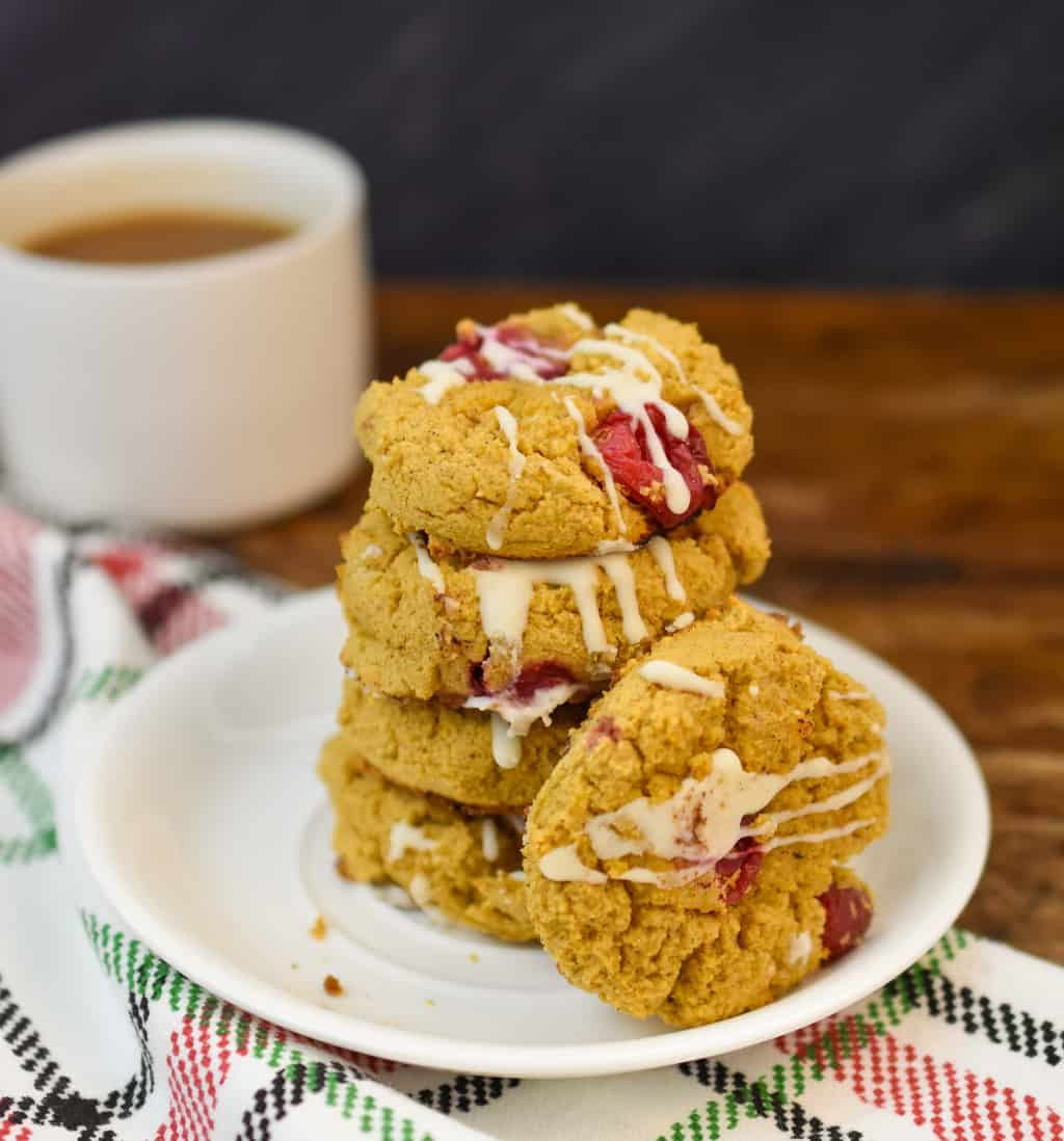 keto pumpkin cranberry cookies stacked on a white plate
