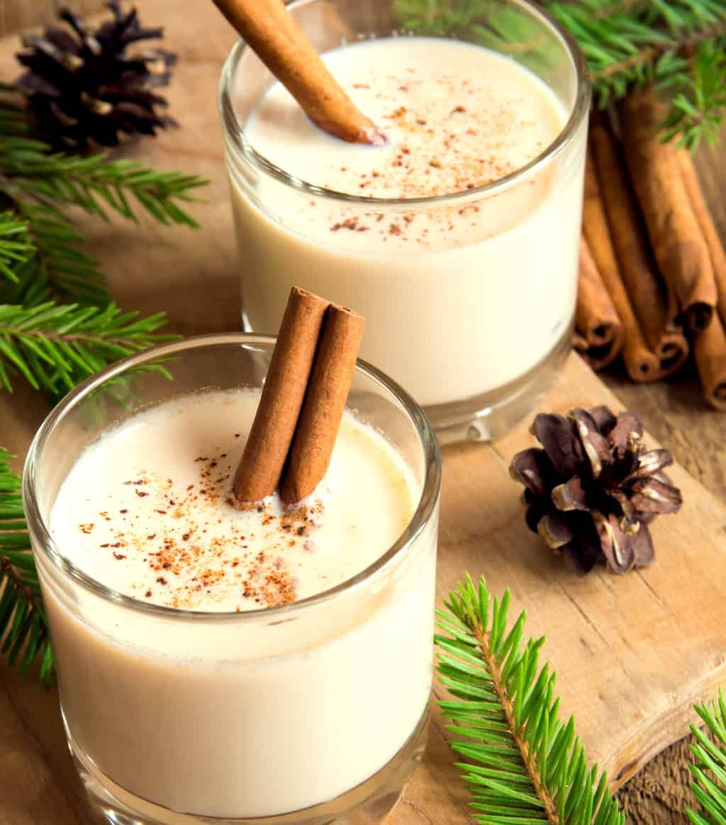 keto eggnog served in two clear glasses with cinnamon sticks
