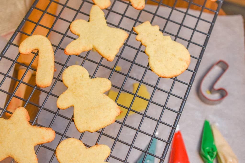 Keto Rolled Sugar Cookies on cooling rack with cookie cutter and icing in background