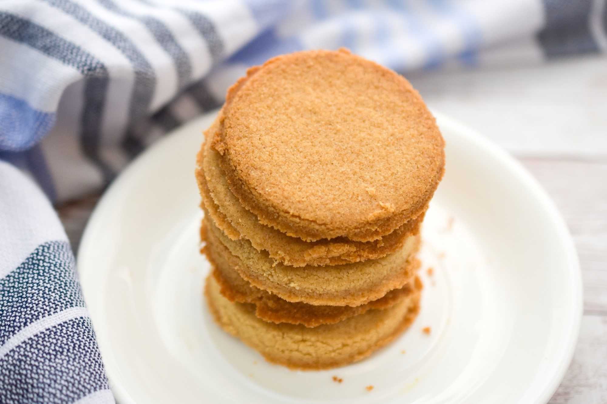 Keto coconut flour shortbread cookies stacked on a white plate