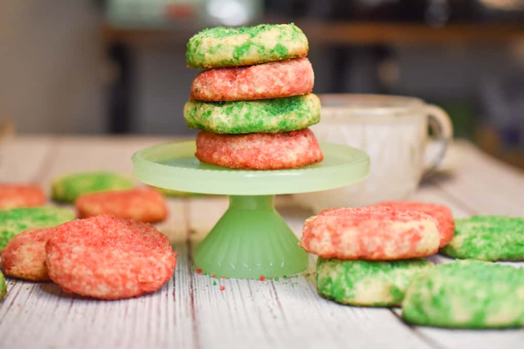 keto soft sugar cookies stacked on green stand and all over table