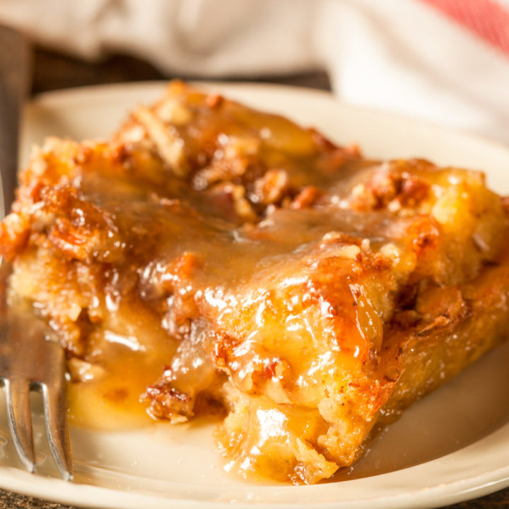 Keto bread pudding with butter rum sauce served on a small white plate