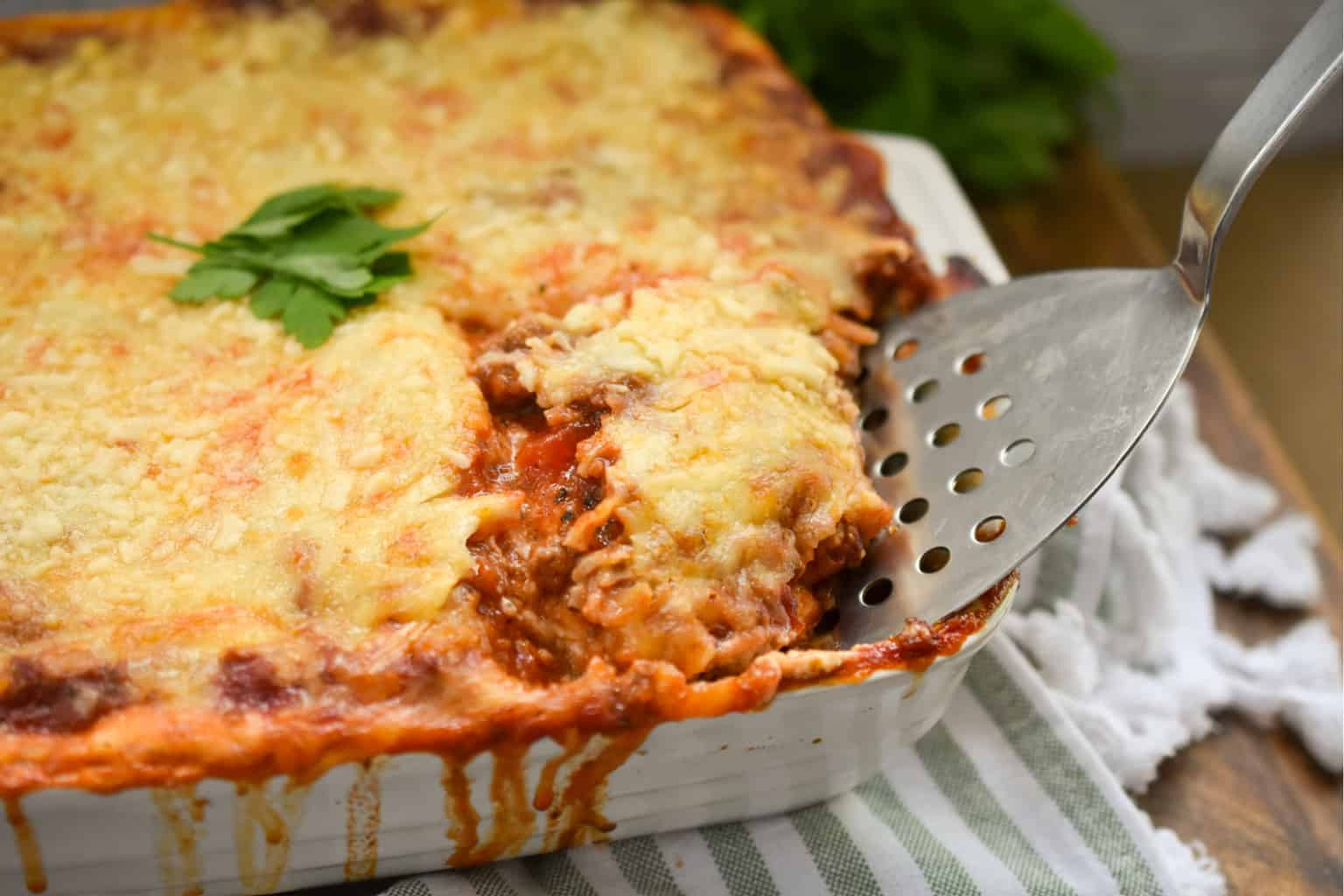 keto crepini lasagna being served from a white square casserole dish