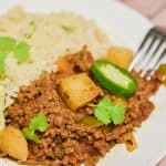 keto Mexican picadillo served cauliflower rice on plate with fork on the side close up