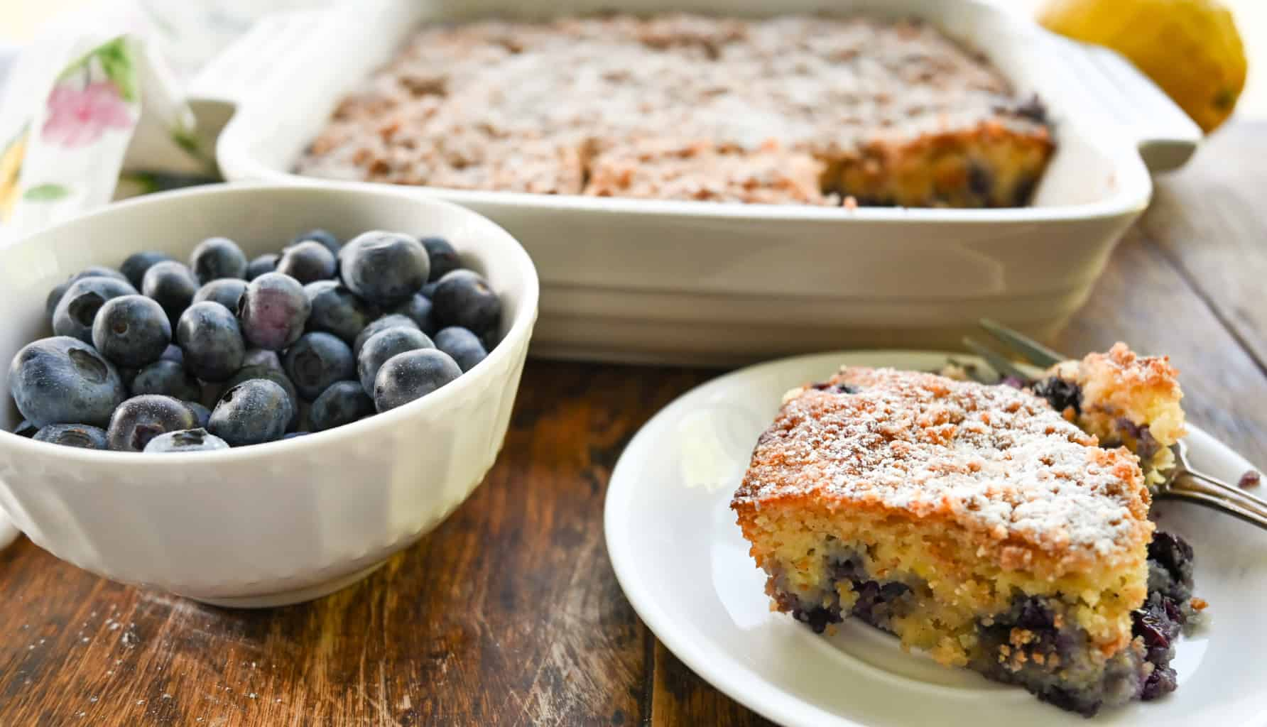 keto blueberry buckle cake with a side of blueberries in a small bowl