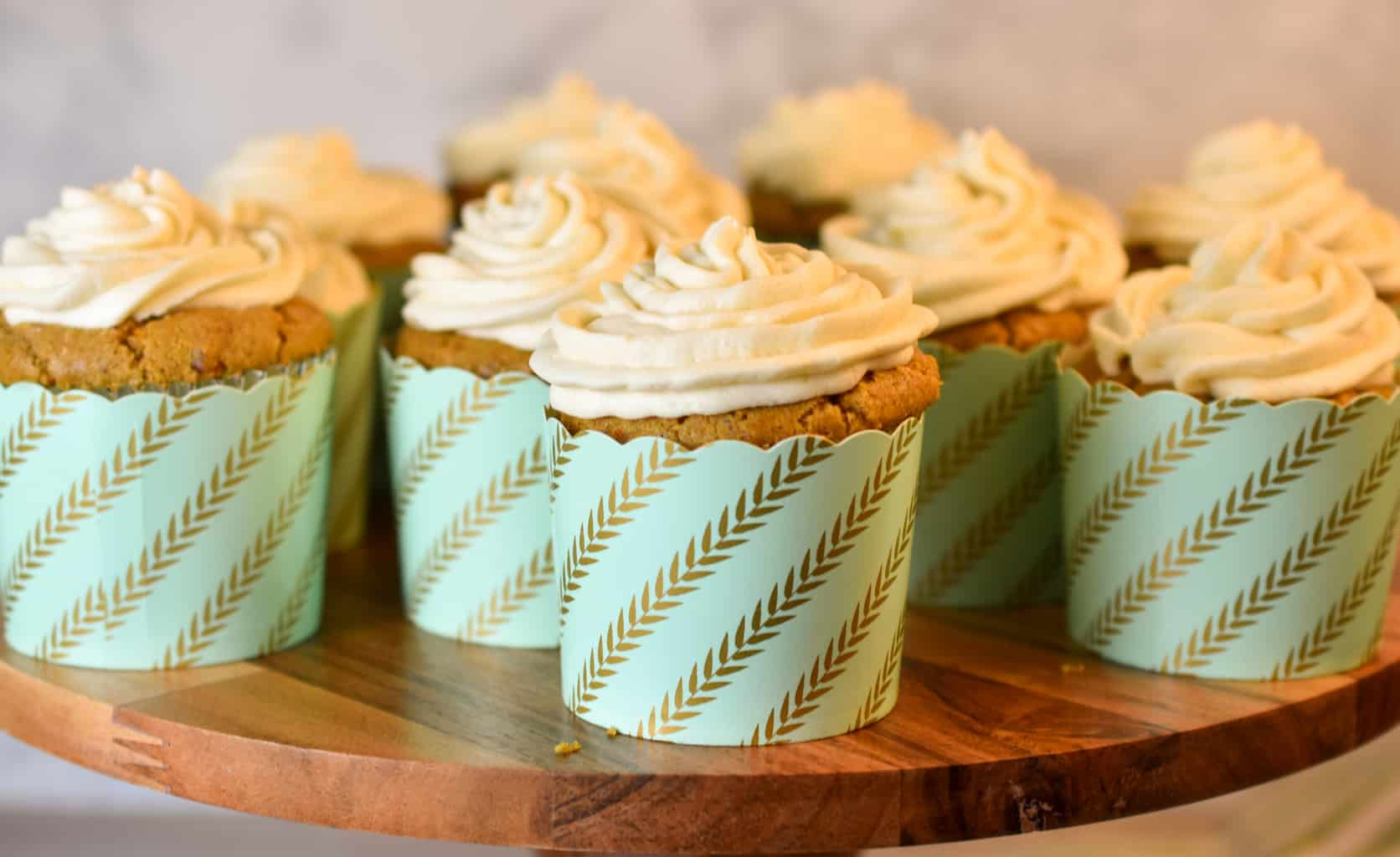 keto carrot cupcakes with cream cheese frosting on a wood cake stand