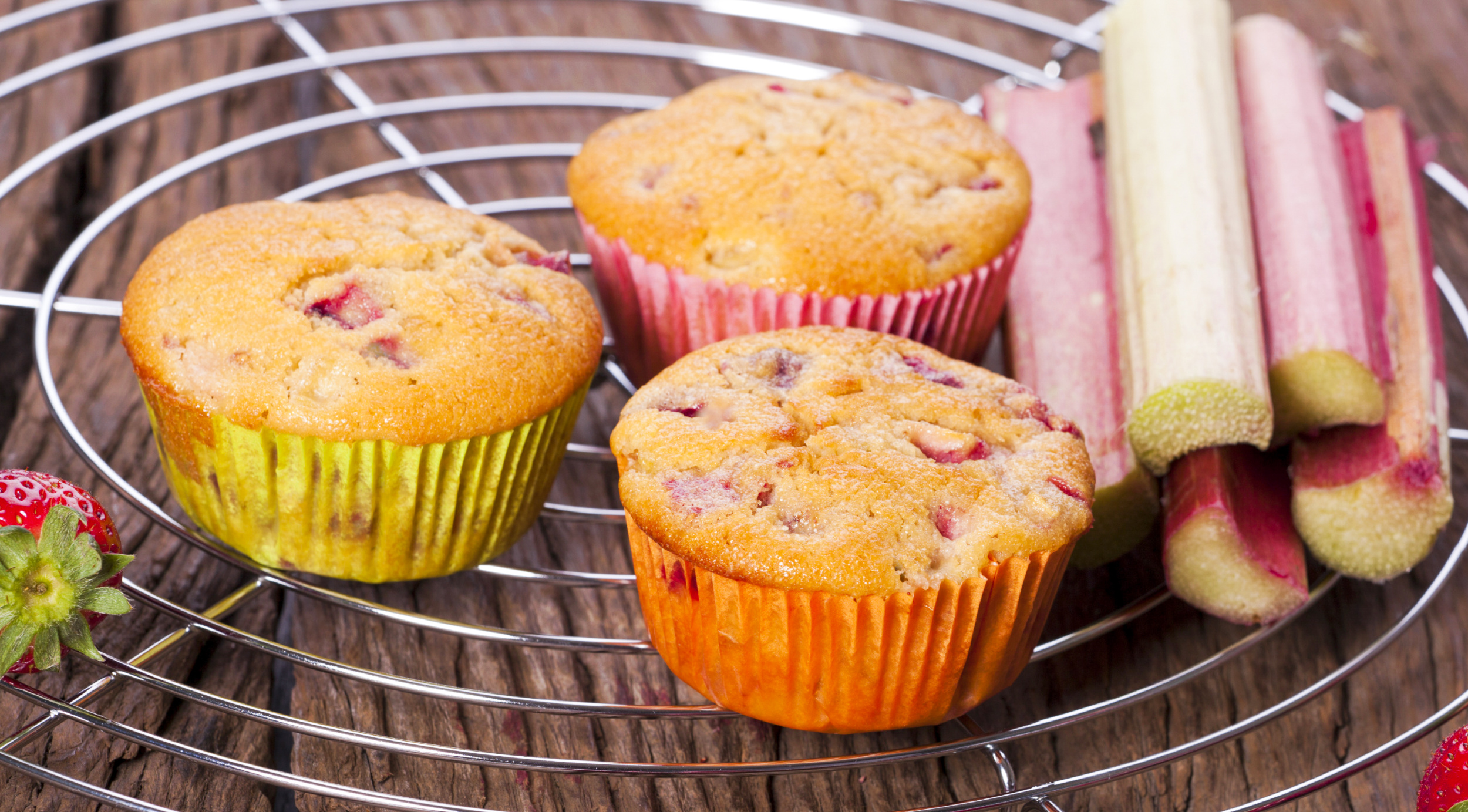 Keto-friendly strawberry rhubarb muffins cooling on a baking rack