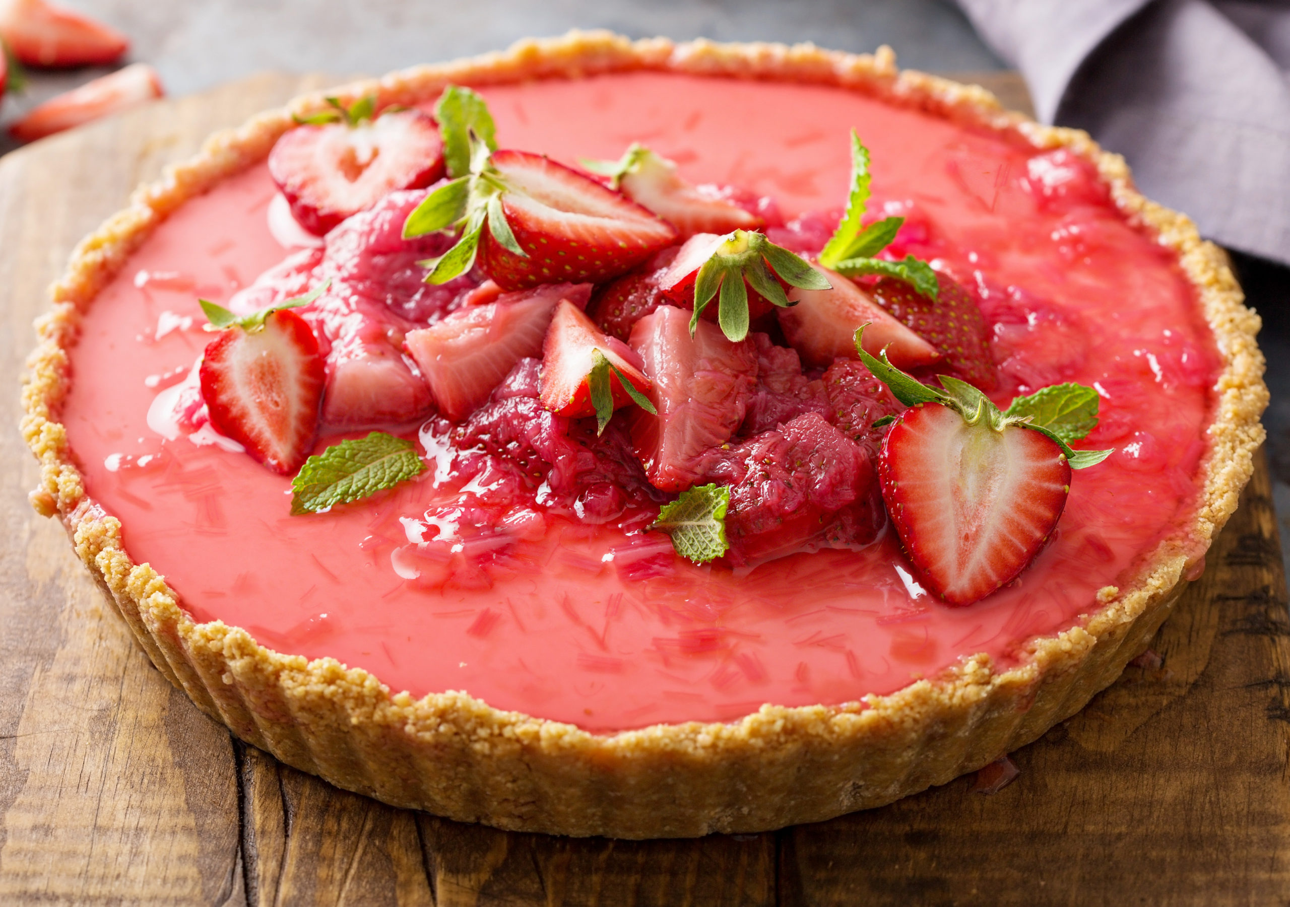 whole keto strawberry cheesecake whole pie displayed on a wood board