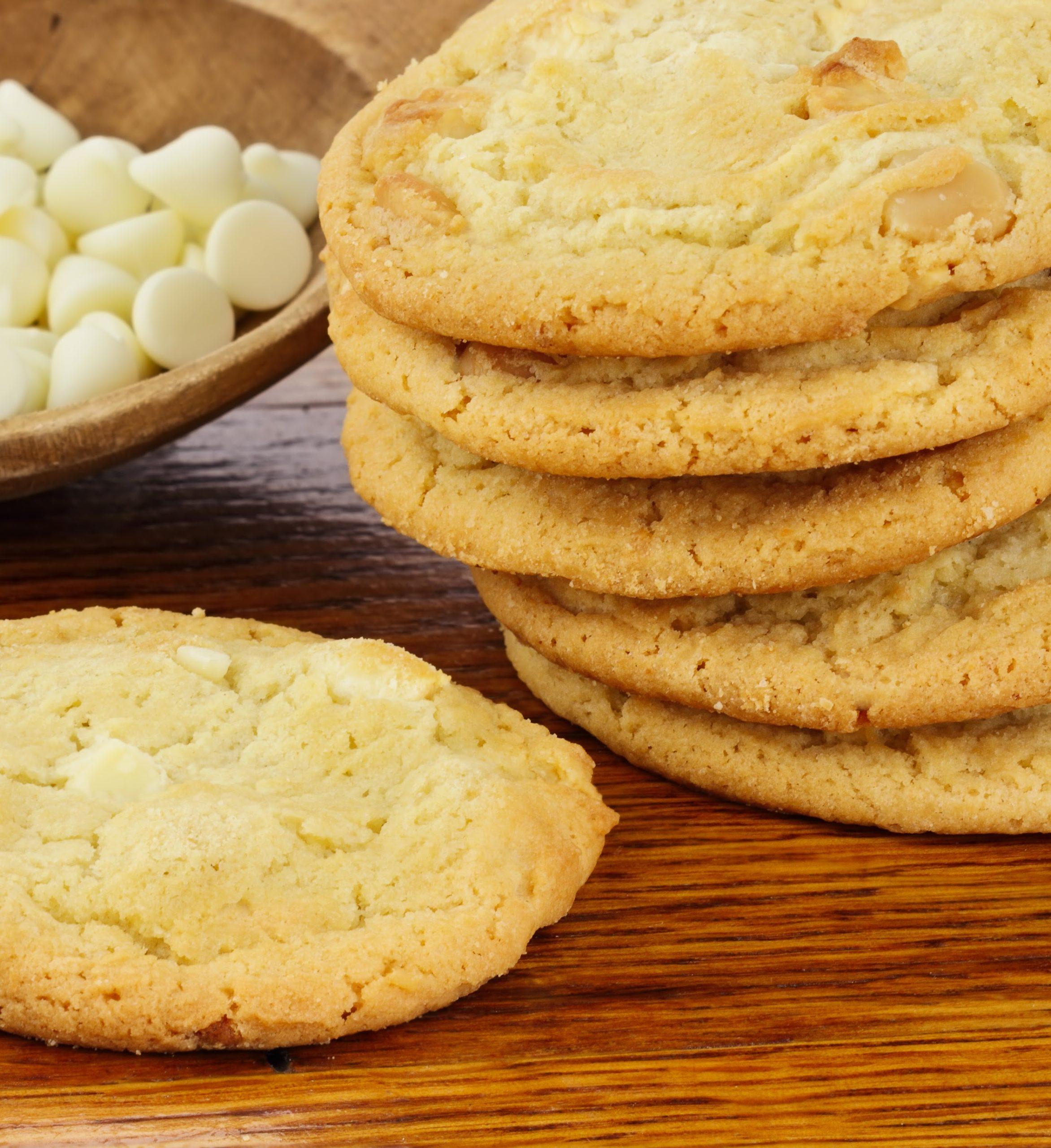 keto white chocolate macademia cookies stacked on wood table