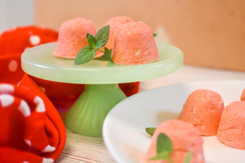 strawberry jello cream cheese fat bombs on green pedestal with mint leaves and red polka dot towel