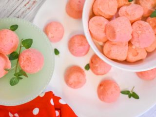 strawberry jello cream cheese fat bombs on white plate with red polka dot towel and mint leaves