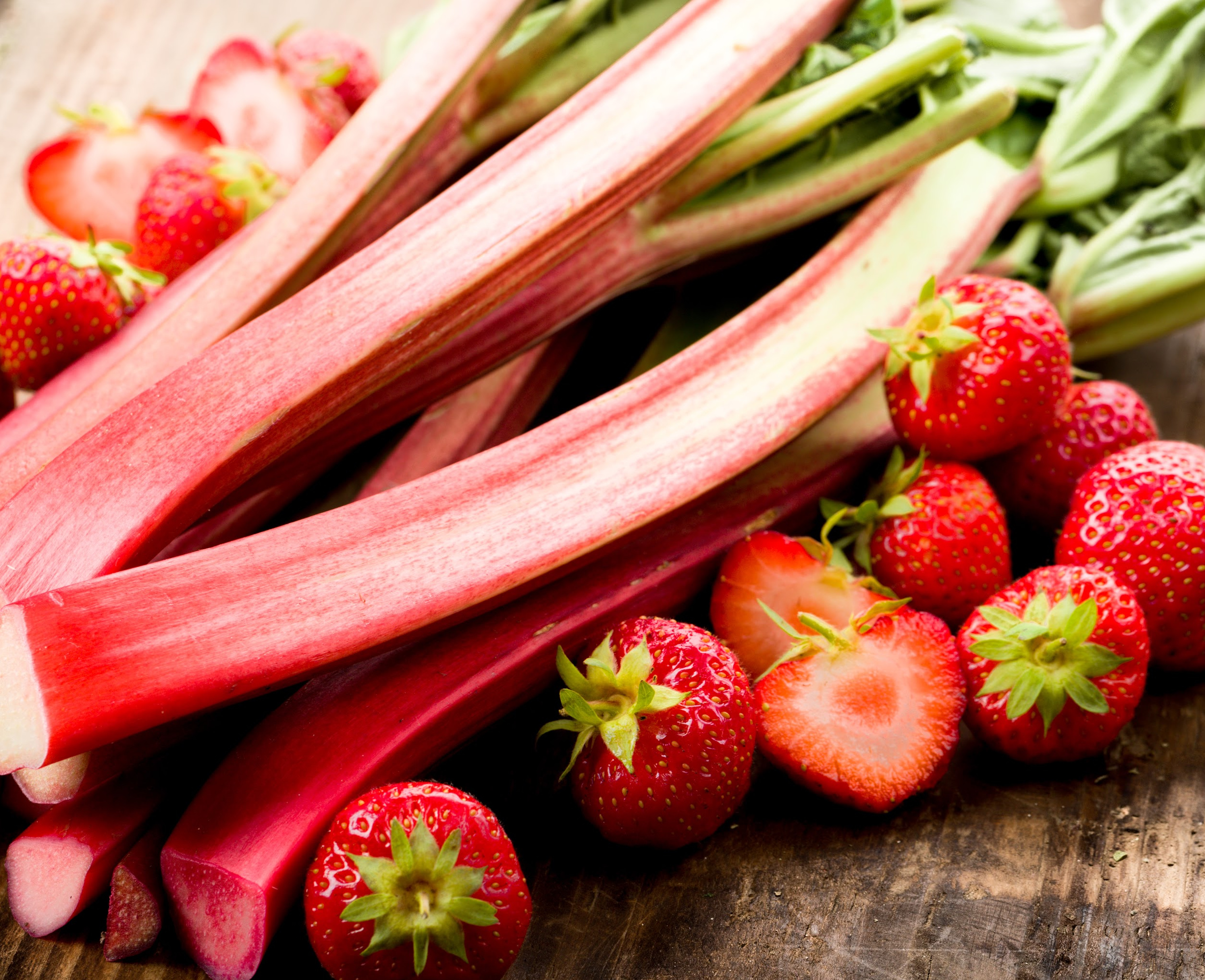Fresh rhubarb and strawberries on a wooden surface