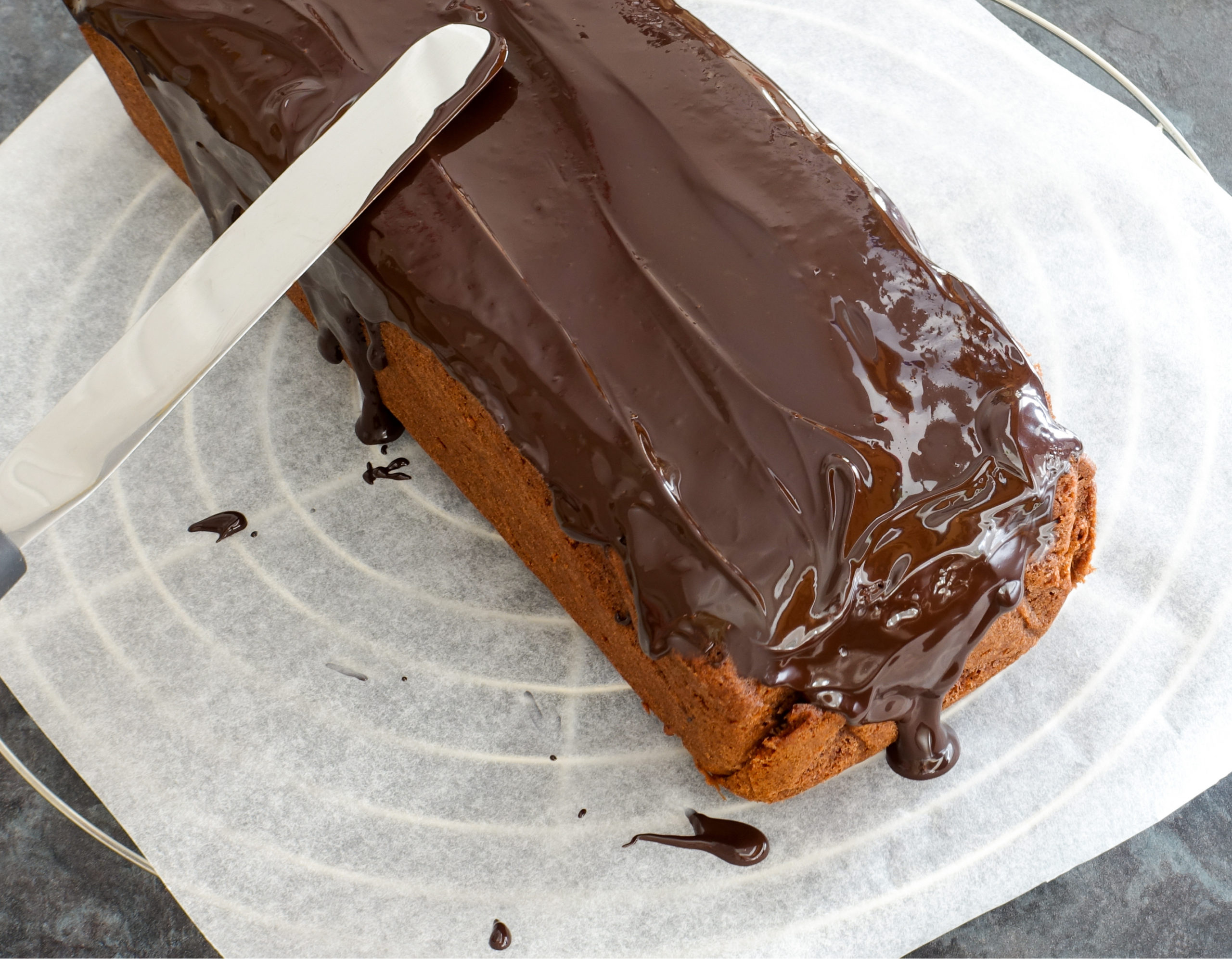 keto sour cream chocolate pound cake with chocolate ganache being smoothed over the top
