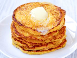 Keto Johnny Cakes stacked on a white plate with a pat of butter melting
