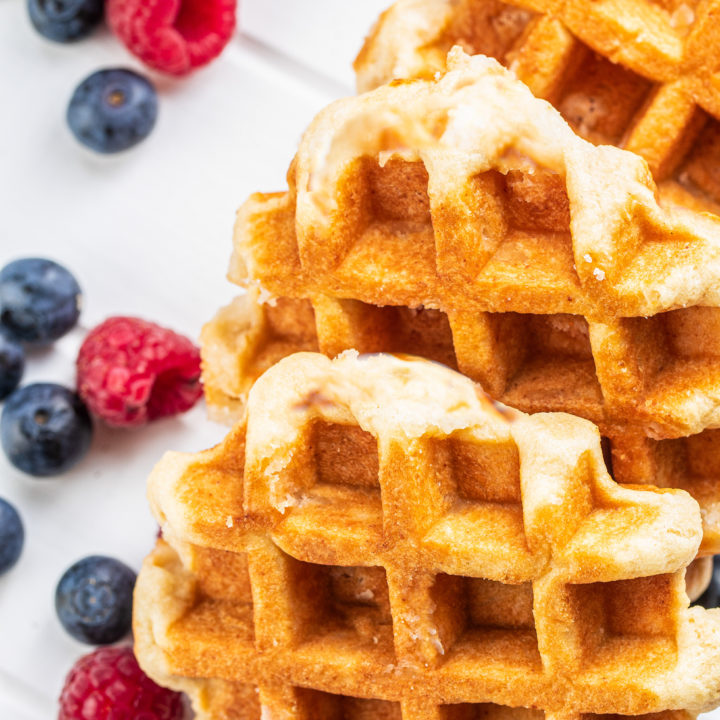Keto Waffles with blueberries and raspberries on white table.