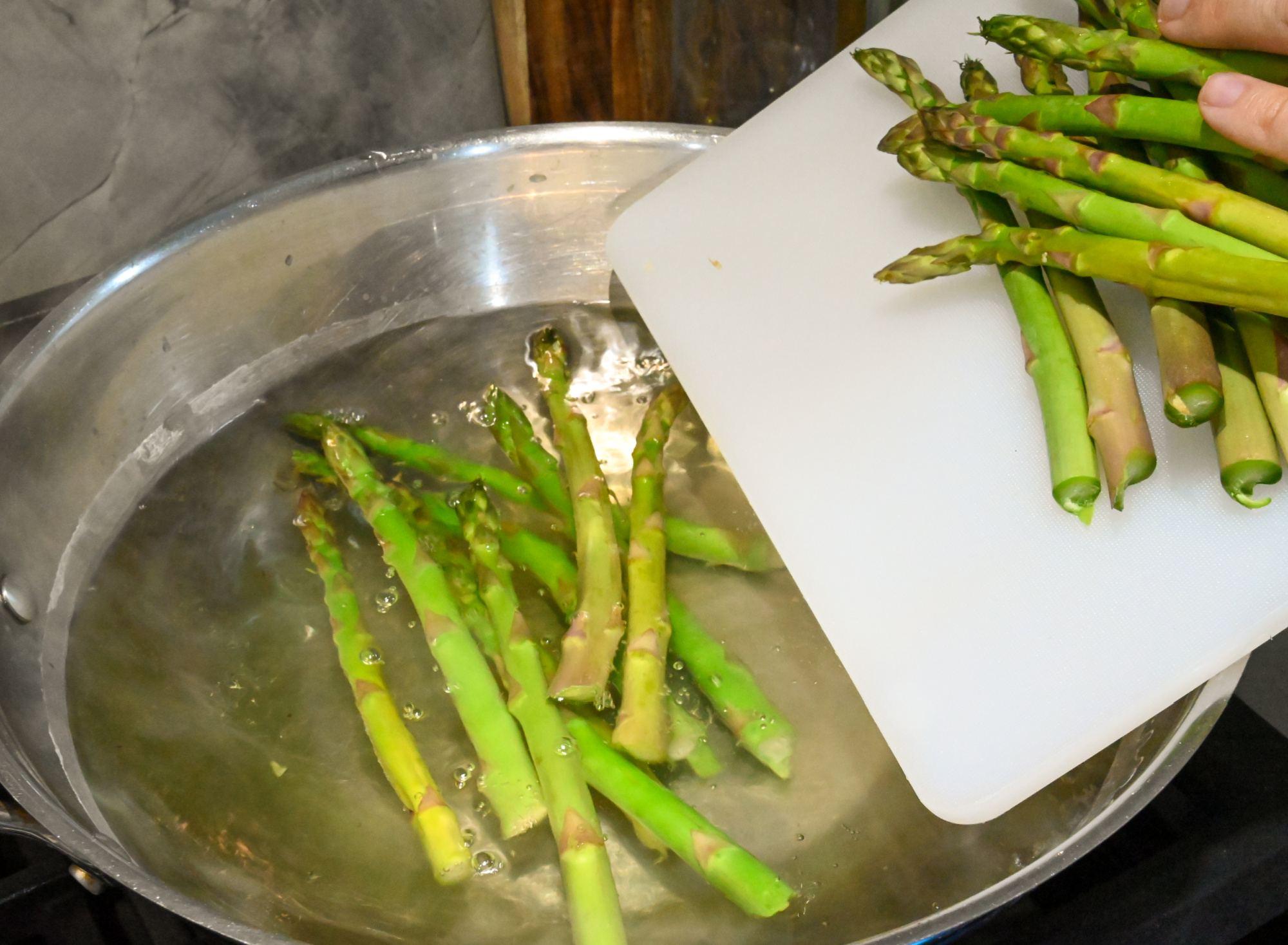 asparagus being blanched in a large wok
