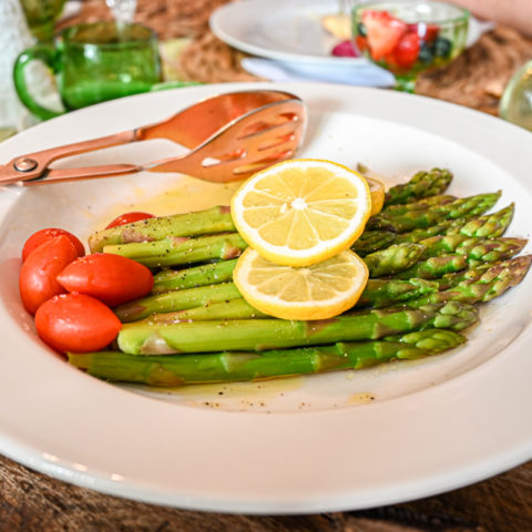 keto asparagus salad served on white platter topped with lemon slices and tomatoes up close