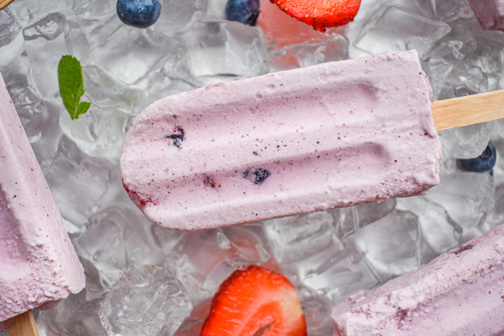 keto berries and cream popsicle on ice up close wirh scattered strawberries and blueberries