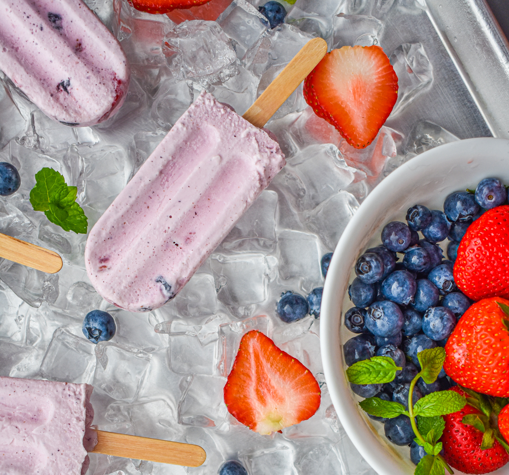keto berries and cream popsicles on ice and white bowl with berries and mint up close