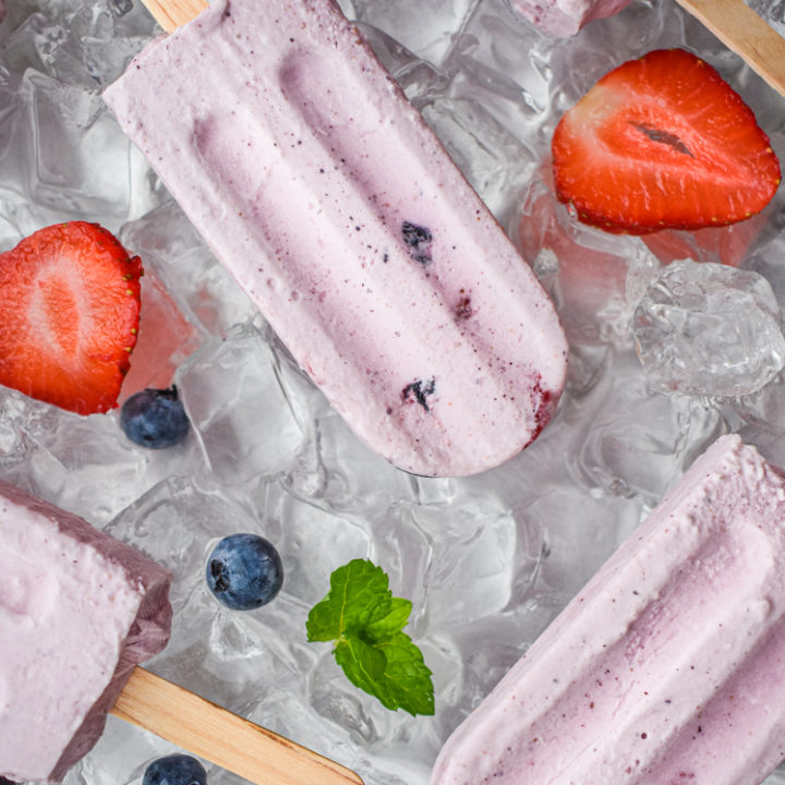 keto berries and cream popsicles on ice with scattered berries on a tray of ice