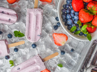 keto berries and cream popsicles on ice with popsicle mold and bowl of berries on the right