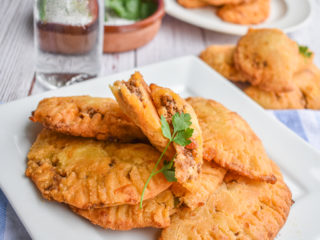 keto ground beef empanadas on white plate up close with more empanandas in the background