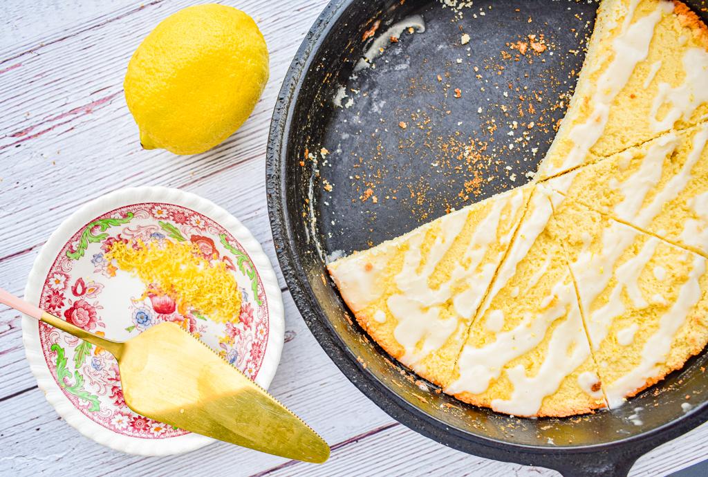 keto lemon ricotta scones in cast iron skillet with dish of lemon zest and lemon on the left