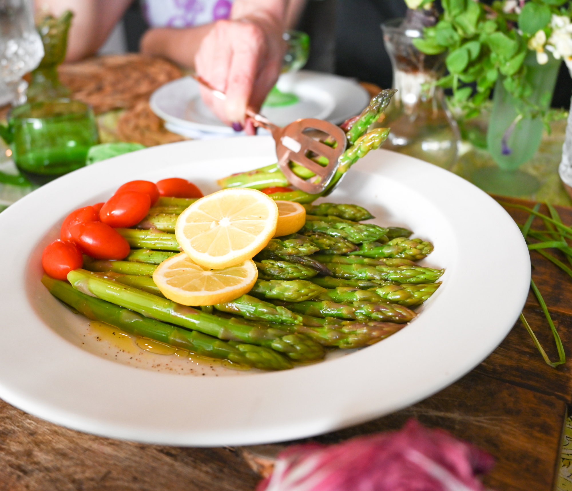 low carb asparagus salad being served with copper salad tongs