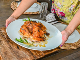 Keto Cuban Mojo Chicken on white plate being placed on wood trivet on table