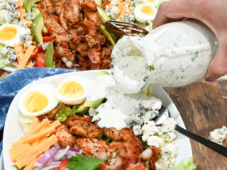 keto Cobb salad with blue cheese dressing being poured on top