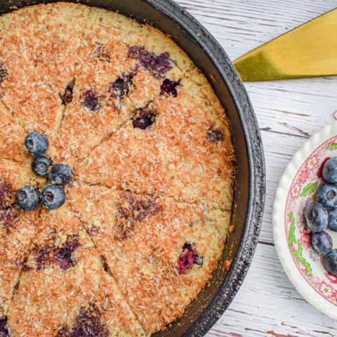 keto blueberry toasted coconut skillet cake in cast iron skillet with dish of blueberries and cake server on the right
